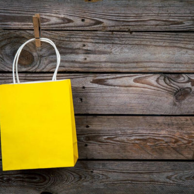 yellow Shopping bag on a wooden background, sale, purchase and