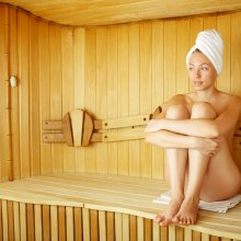 The naked girl sits on a bench in a sauna
