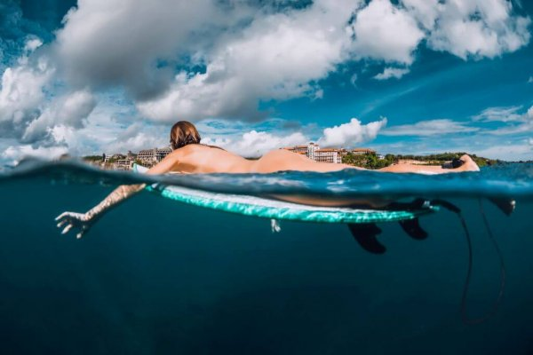 Surf girl floats on surfboard. Naked woman during surfing. Surfer and ocean