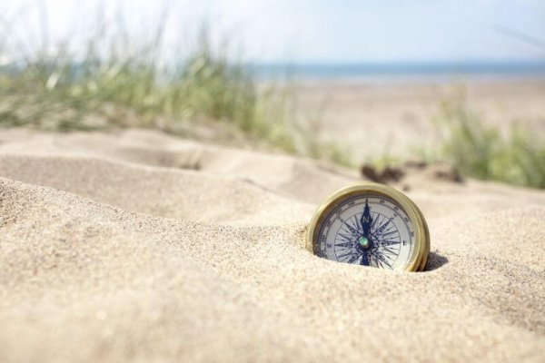 Golden compass buried in the sand on the beach concept for lost or direction