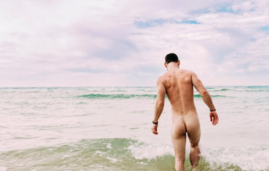 Man paddling in the sea without clothes