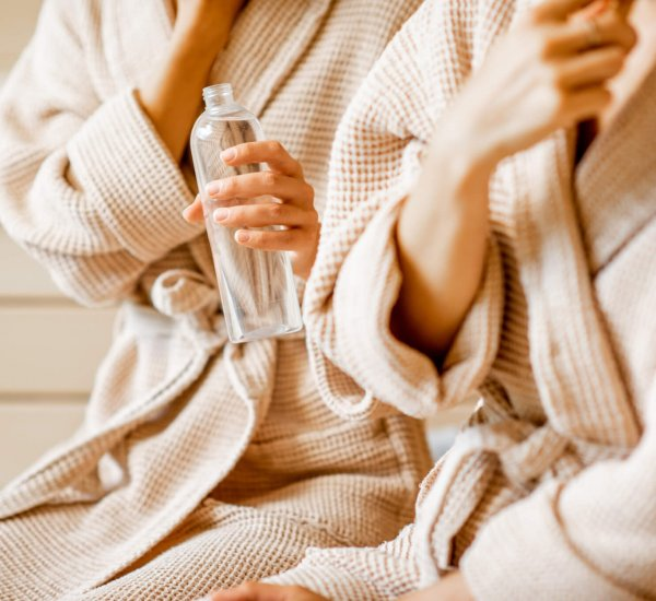 Women in bathrobes taking care of themselves, holding bottle in the SPA. Close-up view