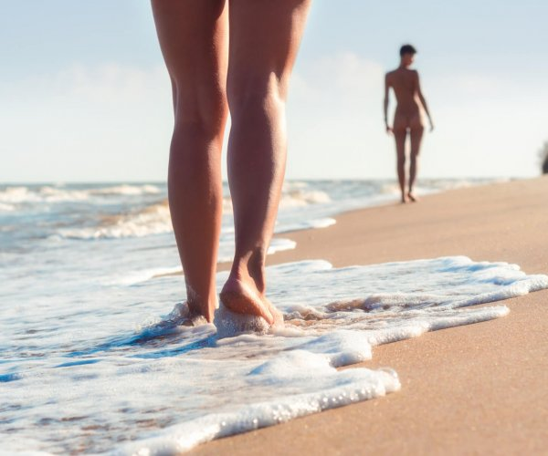 nude young girls walk on the beach in the waves of the surf on a summer day