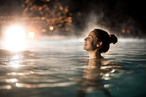 Young happy woman swimming in heated swimming pool during winter night.