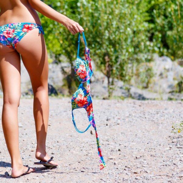 Young thin girl walking on the road in bikini, holding a bra. Legs closeup. Sunny summer day