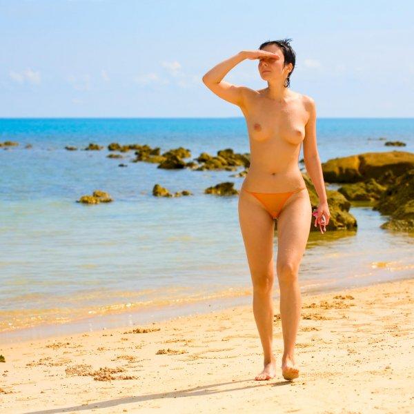 Sunburnt wet female on beach of the tropical sea
