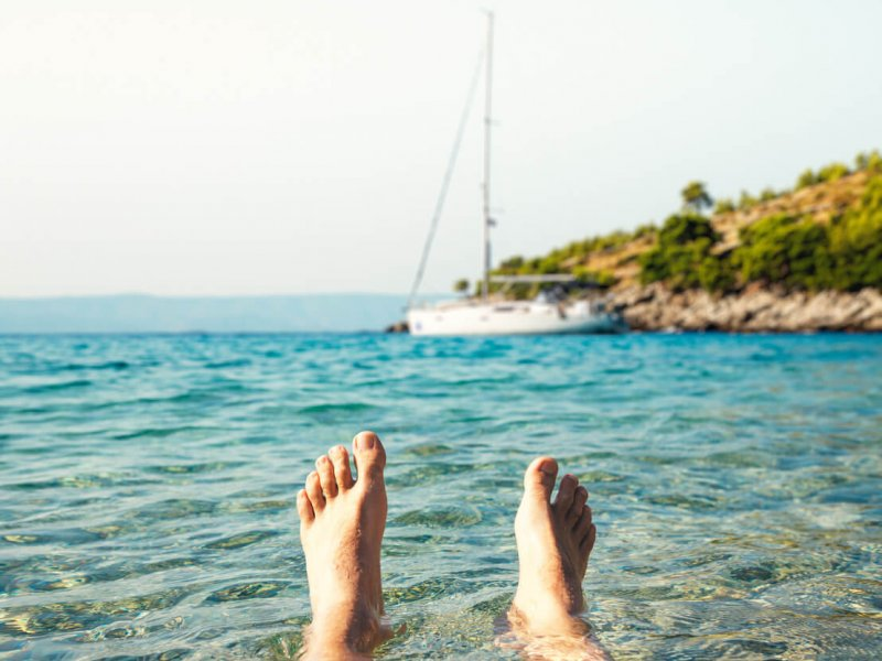 Man lying in the water enjoying summer vacations in remote bay on Brac island.