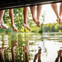 A group of friends legs dangling off a jetty, by the water at a lake together on a sunny afternoon.