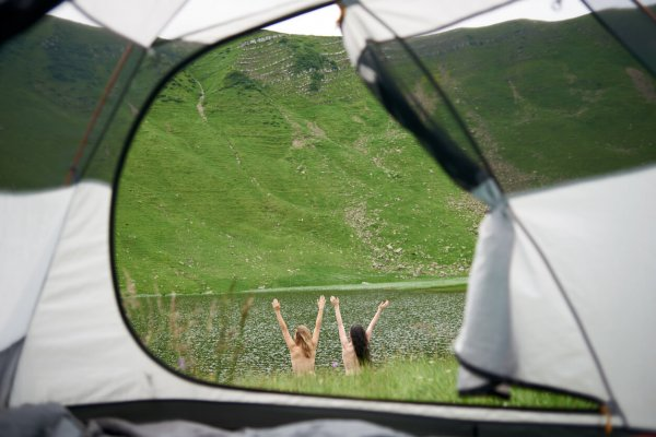 Back view of two attractive naked women lifting hands up in the air near the lake in the mountains. View from tent inside. Lifestyle concept adventure summer vacations outdoor