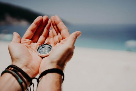 man-39-s-hand-holding-compass-against-the-backdrop-of-beach-and-sea-the-concept-of-travel-summer.jpg