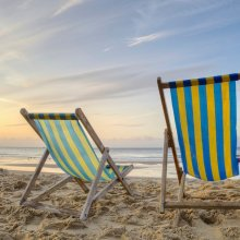 Two Deckchairs On A Beach