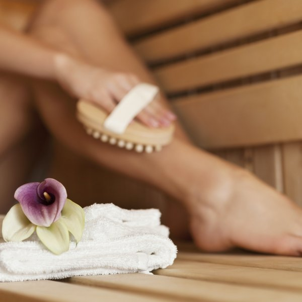 Woman massaging leg in sauna